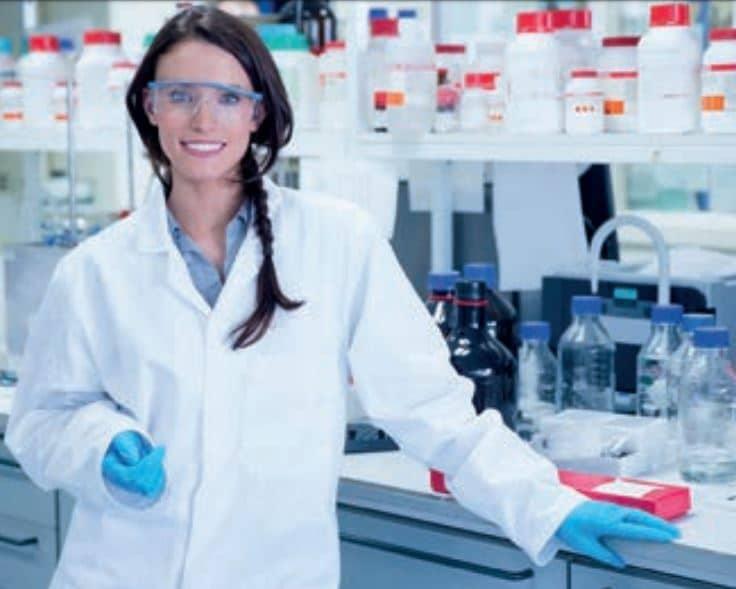 Önlük, eldiven ve gözlük ile kimya laboratuvarında çalışan bir kimyager.